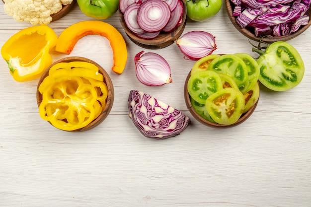 Vista superior verduras frescas cortadas tomates verdes cortados repollo rojo cortado cebolla cortada calabaza coliflor cortada pimiento en tazones sobre superficie blanca