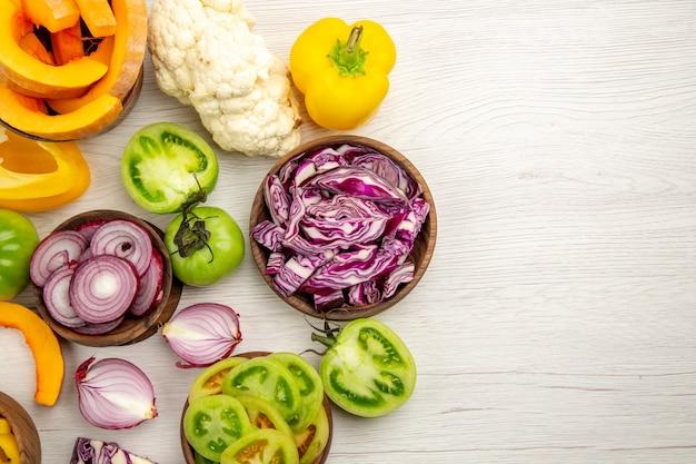 Vista superior verduras frescas cortadas tomates verdes cortados repollo rojo cortado cebolla cortada calabaza coliflor cortada pimiento en tazones sobre superficie de madera blanca con espacio de copia