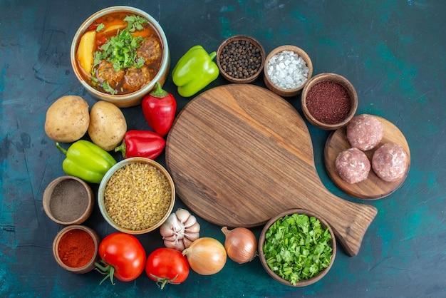 Vista superior de verduras frescas con diferentes condimentos, sopa de carne y verduras en el escritorio azul oscuro
