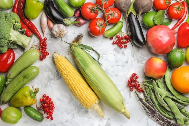 Vista superior de verduras frescas con frutas y maíz sobre fondo blanco.