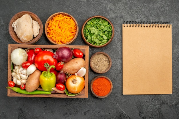 Vista superior de verduras frescas con ingredientes para ensaladas en el escritorio oscuro