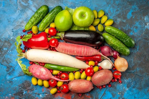 Vista superior de verduras frescas con manzanas sobre fondo azul.
