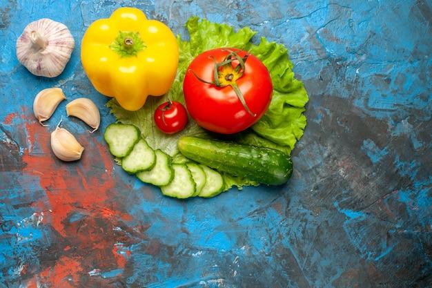 Vista superior de verduras frescas pepino tomate ensalada verde y ajo sobre fondo azul.