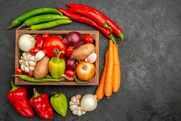 Vista superior de verduras frescas con pimienta y ajo en la mesa oscura salud de color de ensalada madura
