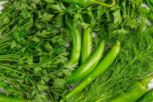 Vista superior de verduras frescas con pimientos sobre fondo blanco.