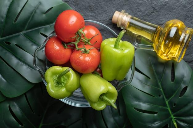 Vista superior de verduras frescas en un tazón de vidrio y una botella de aceite sobre fondo negro con hojas verdes.