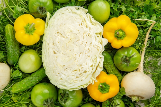 Vista superior de verduras frescas con tomates verdes, rábano y pimientos sobre fondo blanco.