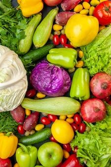 Vista superior de verduras y frutas calabacín pimientos manzanas membrillo tomates cherry cumcuat perejil col limón granadas