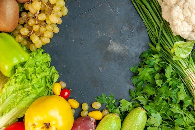 Vista superior de verduras y frutas, lechuga, calabacín, pimientos, membrillo, kiwi, uvas, perejil, cebolla verde, coliflor, espacio libre