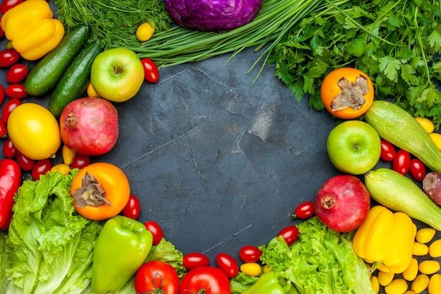 Vista superior de verduras y frutas, lechuga, tomates, calabacín, pepino, eneldo, tomates cherry, pimientos, granada, caqui, manzana, lugar libre en el centro