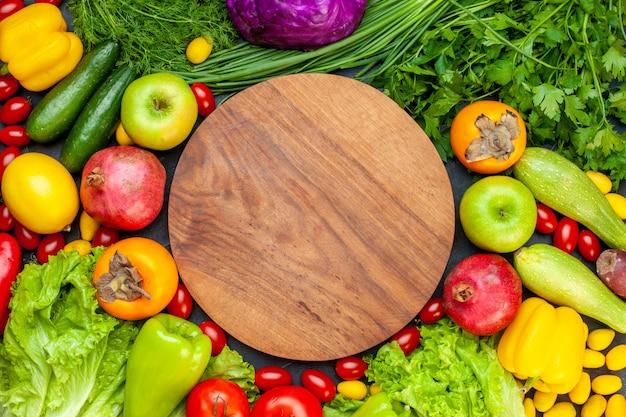 Vista superior de verduras y frutas, lechuga, tomates, pepino, eneldo, tomates cherry, calabacín, cebolla verde, perejil, granada, caqui, manzana, tablero de madera redonda en el centro