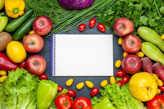 Vista superior de verduras y frutas lechuga tomates pepino eneldo tomates cherry calabacín cebolla verde perejil manzana limón kiwi cuaderno en el centro
