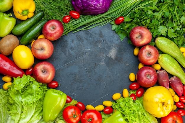 Vista superior verduras y frutas lechuga tomates pepino eneldo tomates cherry calabacín cebolla verde perejil manzana limón kiwi espacio libre en el centro