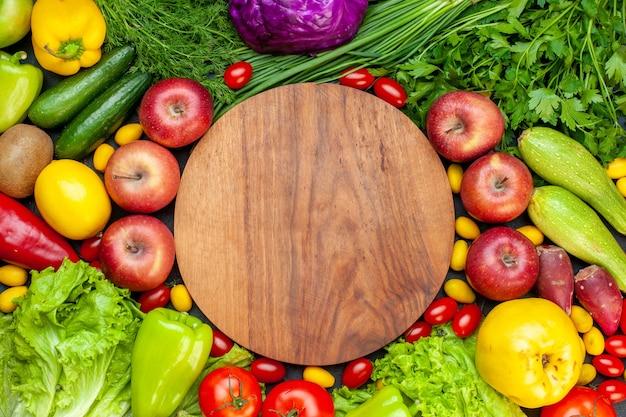 Vista superior de verduras y frutas, lechuga, tomates, pepino, eneldo, tomates cherry, calabacín, cebolla verde, perejil, manzana, limón, kiwi, tablero de madera redonda en el centro