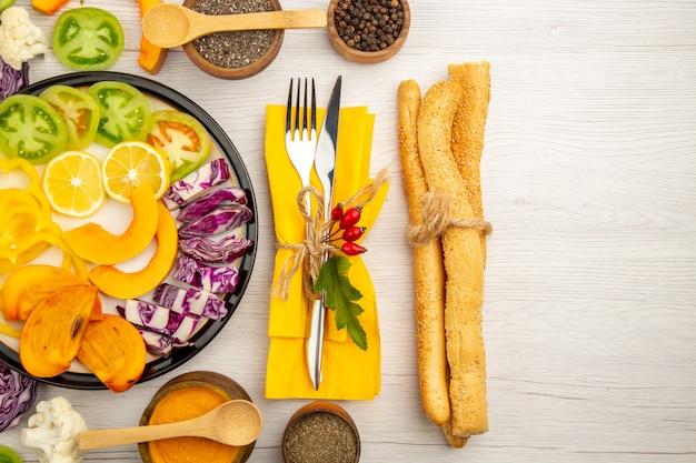 Vista superior de verduras y frutas picadas calabaza pimientos caqui repollo rojo tomates verdes en plato negro varias especias en cuencos tenedor y cuchillo en pan de servilleta amarillo sobre mesa blanca
