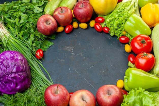 Vista superior de verduras y frutas, tomates cherry, manzanas cumcuat, repollo morado, cebolla verde, lechuga, perejil, pimientos con lugar libre