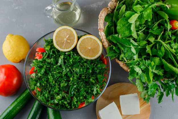 Vista superior de verduras picadas en un recipiente de vidrio con tomate, queso, limón sobre superficie gris