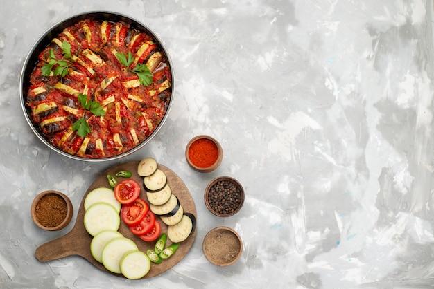 Vista superior de verduras en rodajas como tomates y berenjenas frescas y cocidas en el escritorio blanco comida vegetal fresca madura