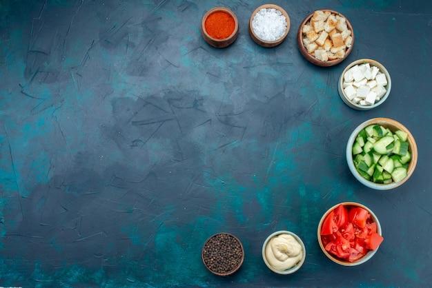 Vista superior de verduras en rodajas con condimentos en el color de ensalada de verduras de fondo azul oscuro