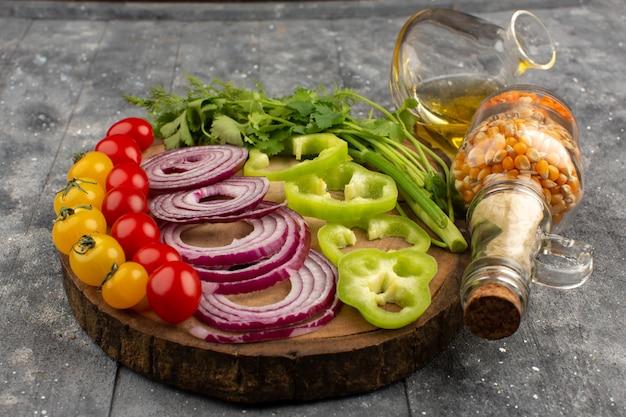 Vista superior verduras en rodajas enteras frescas en el piso gris