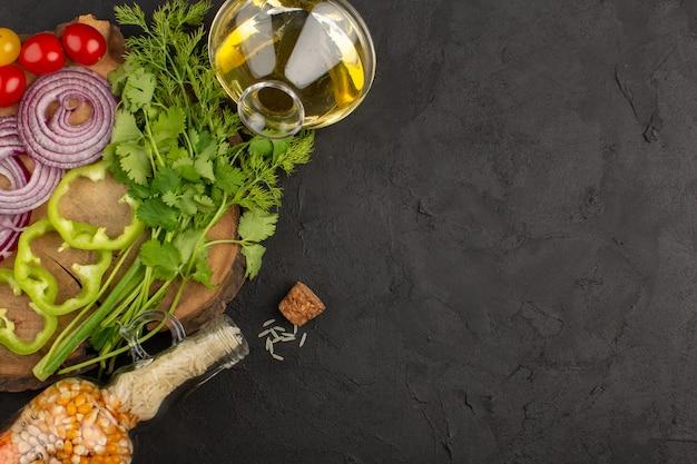 Vista superior de verduras en rodajas y frescas como cebollas tomates y pimientos sobre el fondo gris