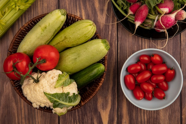 Vista superior de verduras saludables como calabacín, pepino y coliflor en un balde con tomates en un recipiente con rábanos en un plato sobre una pared de madera