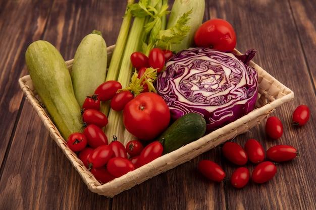 Vista superior de verduras saludables como tomates, apio, repollo morado y calabacines en un balde sobre un fondo de madera