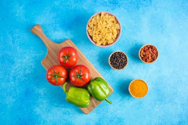 Vista superior. verduras sobre tabla de madera y especias con pasta cruda sobre superficie azul.