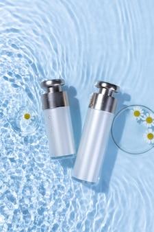 Vista superior vertical de botellas de cuidado de la piel sobre una superficie de agua azul claro