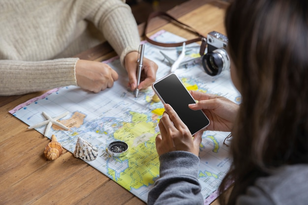 Vista superior de los viajeros que planean en vacaciones para viaje de vacaciones con mapa, concepto de viaje