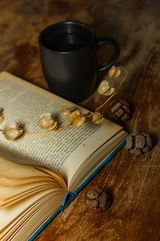 Vista superior de un viejo libro con taza de café y flores secas en la mesa de madera. vertical
