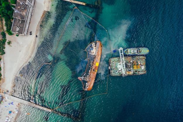 Vista superior de un viejo petrolero que encalló y volcó en la orilla cerca de la costa