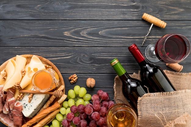 Vista superior vino con comida y racimos de uva