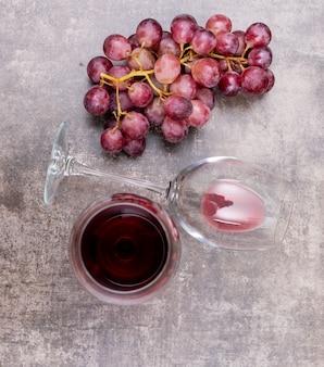 Vista superior vino tinto en copas y uva en piedra oscura vertical
