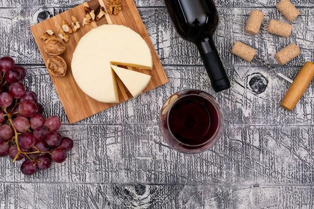 Vista superior vino tinto con uva y queso a bordo y en madera blanca horizontal