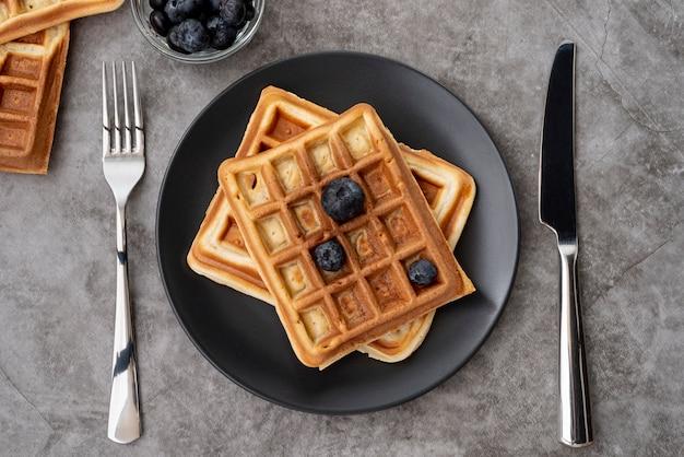 Vista superior de waffles en placa con arándanos y cubiertos