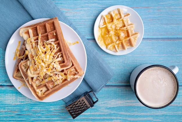 Vista superior de waffles en placa con queso rallado y bebidas
