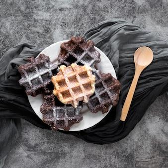 Vista superior de waffles en plato con cuchara y tela