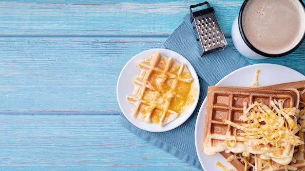 Vista superior de waffles en plato con queso rallado