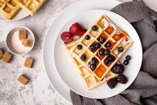Vista superior de waffles en plato con surtido de frutas y terrones de azúcar