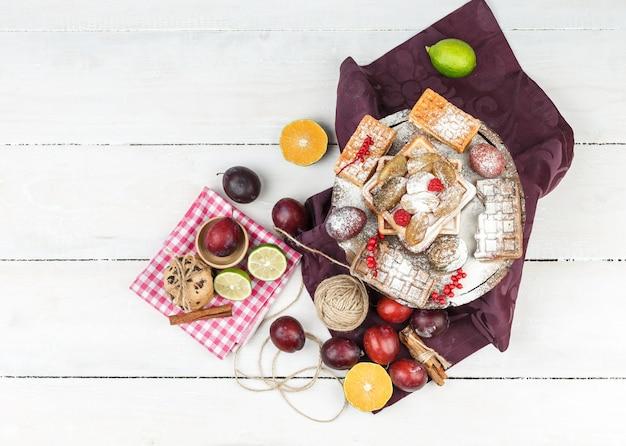 Vista superior de waffles sobre mantel burdeos con cítricos, ovillo, canela y tazón de ciruelas en la superficie de la tabla de madera blanca.