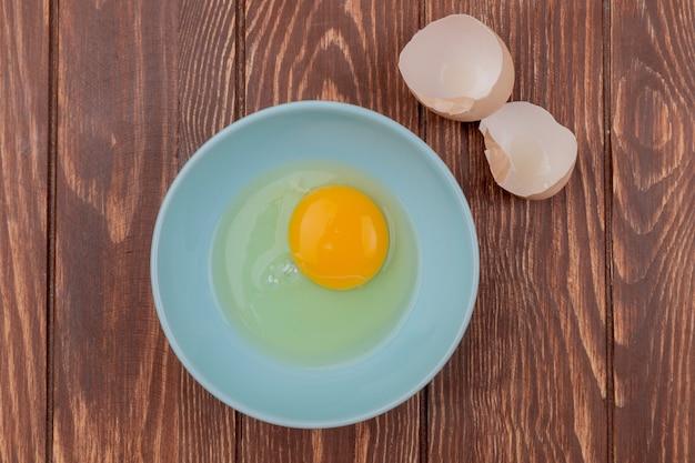 Vista superior de la yema de huevo y la clara en un tazón blanco con cáscaras de huevos sobre un fondo de madera