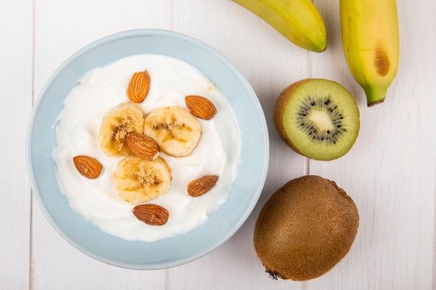 Vista superior de yogur con plátanos y almendras y kiwis frescos en madera blanca