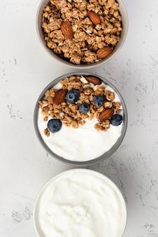 Vista superior de yogurt de desayuno con cereales y arándanos