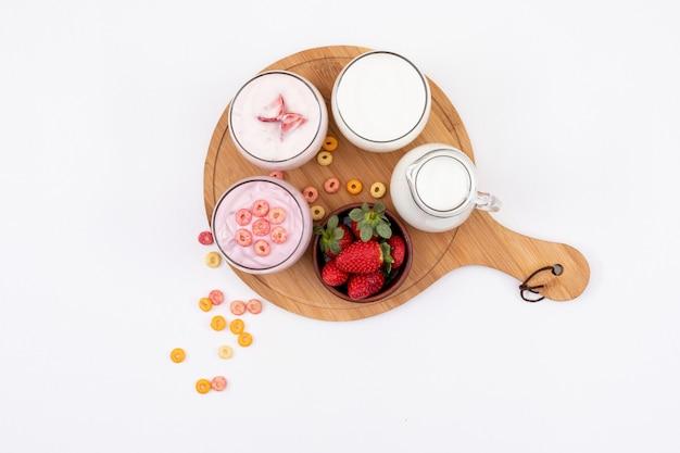 Vista superior de yogurt con leche y fresa en tabla de cortar de madera sobre una superficie blanca horizontal