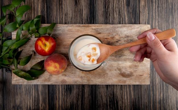 Vista superior de yogurt en un vaso con cuchara de madera y duraznos maduros frescos sobre tabla de madera sobre fondo rústico