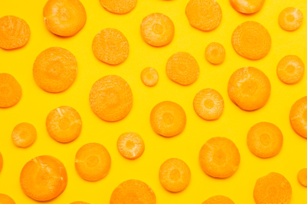 Vista superior de zanahoria en rodajas sobre fondo amarillo