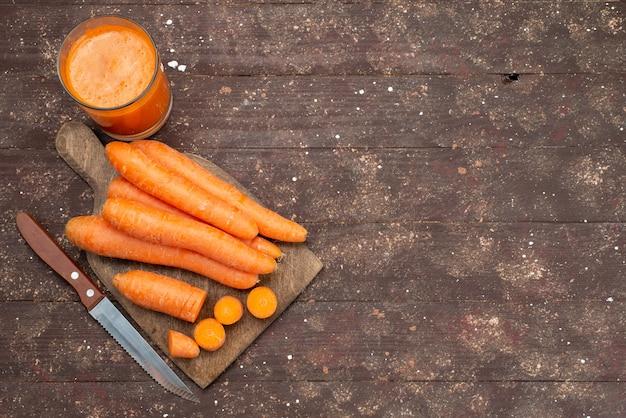Vista superior de zanahorias anaranjadas en rodajas y enteras con jugo de zanahoria fresco en marrón