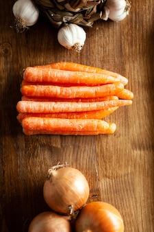 Vista superior de zanahorias frescas junto a cebolla blanca y ajo sobre mesa de madera rústica. ingredientes frescos