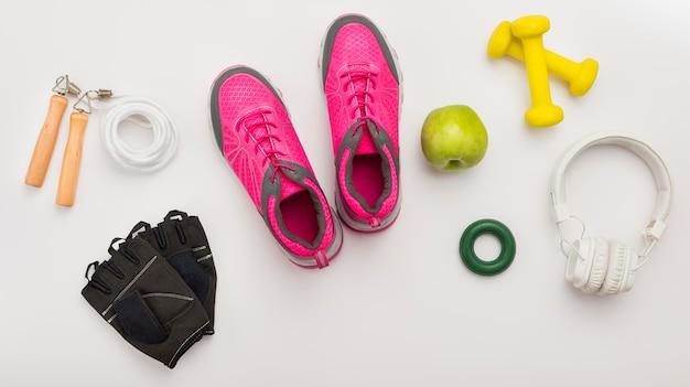 Vista superior de zapatillas con guantes de gimnasia y auriculares